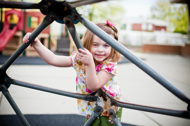 A little girl in a floral shirt and green plants climbs up a jungle gym.