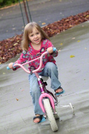 A little girl with light brown hair rides on a pink bike with training wheels.