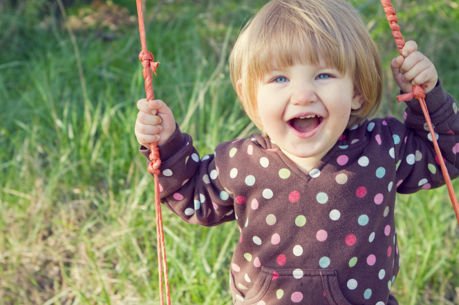 A little girl with short brown hair and a polka-dot sweater plays on a swing.