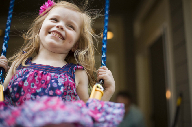 A little girl with light brown hair and a floral dress smiles while holding on to both chains on her swing.