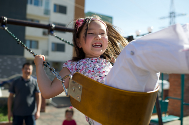 A little girl from Mongolia swinging on a yellow swing with her father standing behind her.