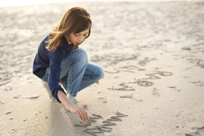 A girl wearing a blue shirt and jeans bends down in the sand and draws in it as the wind blows her hair.