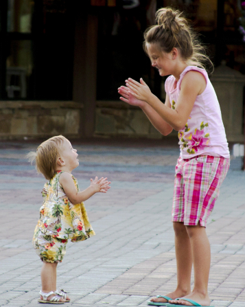 A girl stands outside with her baby sister and plays a clapping game with her.