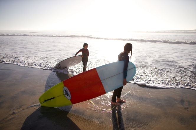 Two girls wearing wet suits carry their surfboards toward the water on a beach.