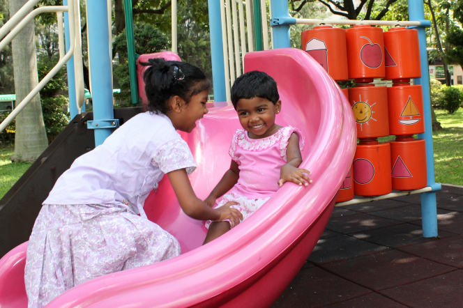 An older girl helps her younger sister play on a pink slide on a playground.