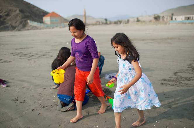 Two sisters walk in the sand on a beach in Peru while holding sand toys.