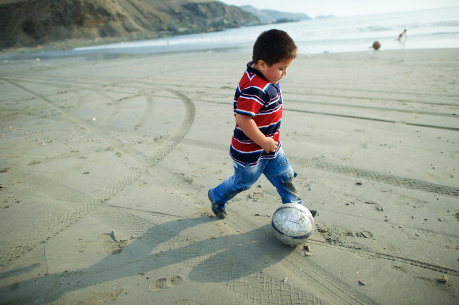 A boy in a striped shirt, jeans, and tennis shoes kicks a soccer ball on the beach.