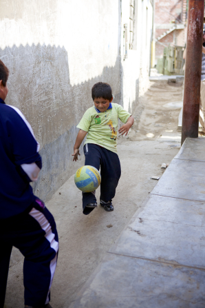 Two Peruvian boys playing soccer together in a small alleyway with one juggling the soccer ball on his foot.