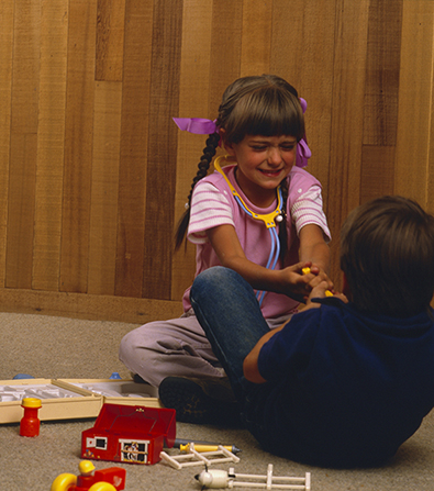 A girl with two braids sitting across from a young boy, each trying to pull a toy away from each other.