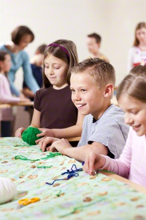 A group of children smile and hold yarn while working on a quilt together.