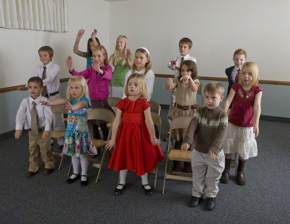 A group of children standing in front of their chairs and singing while making hand motions in Primary.