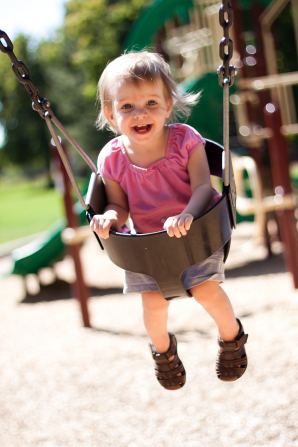 A toddler girl plays on a brown swing at a playground.