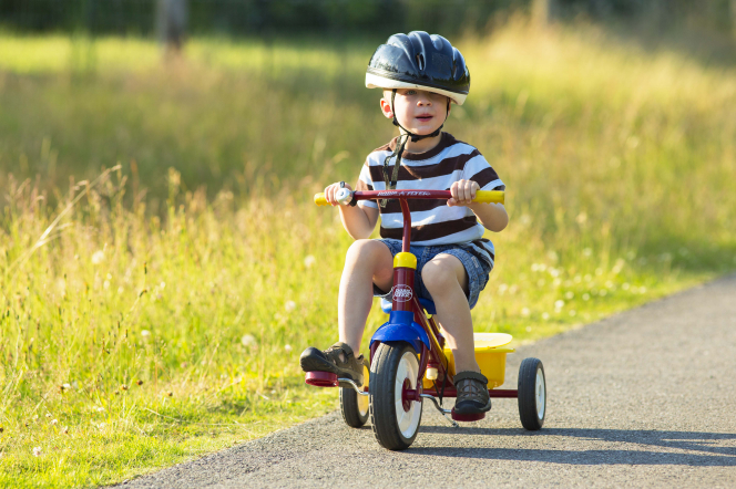 A little boy in a striped shirt and helmet rides a red tricycle down a trail lined with yellow weeds.