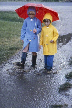 Two girls in raincoats and holding a red umbrella play in the rain.