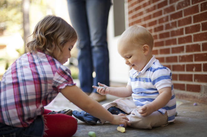 A sister helps her baby brother draw with chalk on the ground near a brick wall.