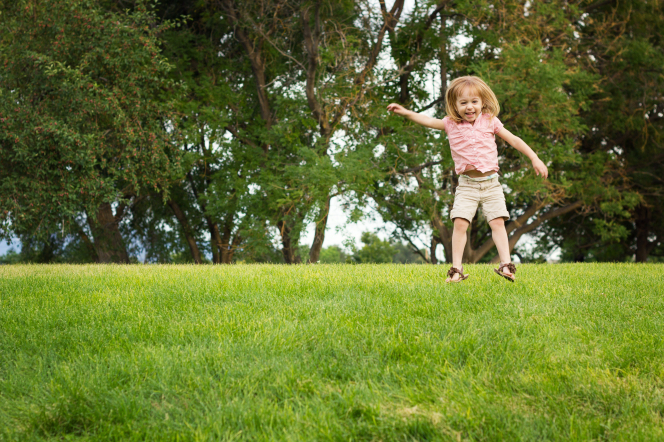 A little girl in a shirt, shorts, and sandals jumps up and down in the grass near a row of trees.