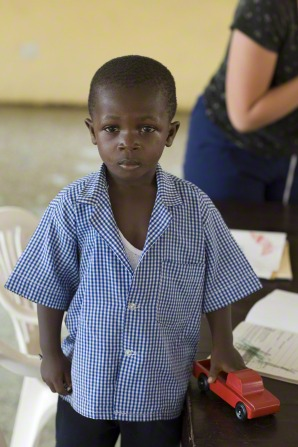 A little boy from Africa stands in a blue button-up shirt and holds a red toy truck in his hand.