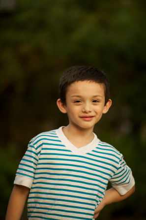 A portrait of a young boy wearing a white and blue striped shirt.