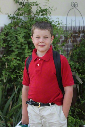A portrait of a young boy wearing a red shirt, white pants, and a black backpack while standing outside.