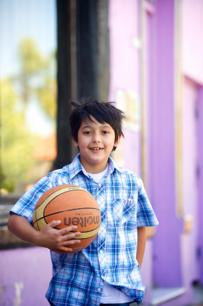 A young boy in a blue and white plaid shirt stands outside holding a basketball in one arm.