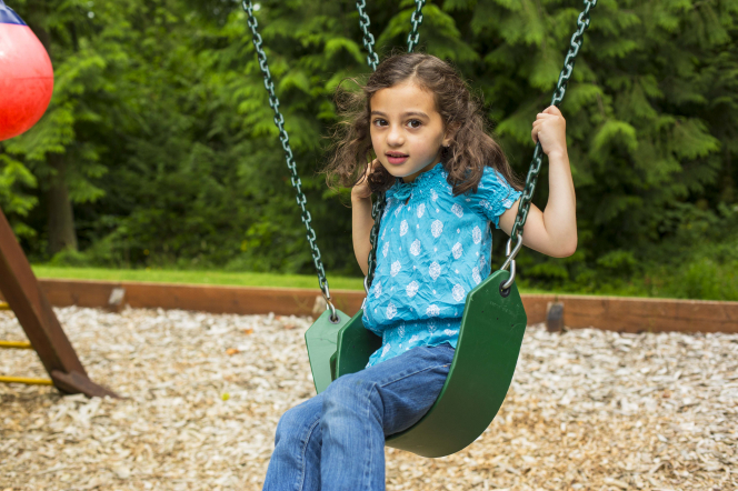 A young girl in a blue shirt and jeans swinging in a green swing.