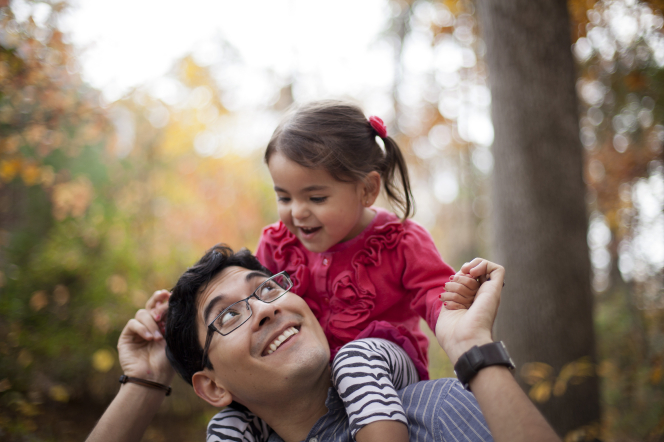 A father with glasses holds his daughter's hands and smiles up at her as she sits on his shoulders.