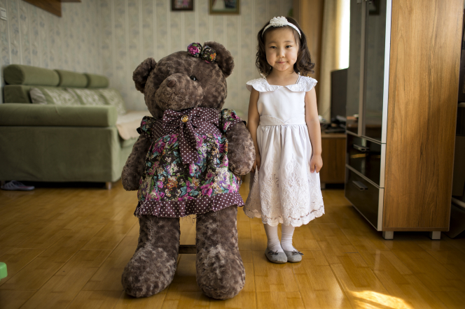 A little girl in a white dress standing next to a brown teddy bear the same height as her, wearing a floral dress.