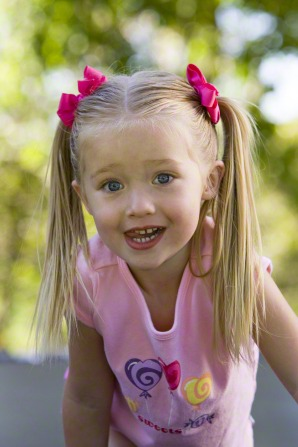 A little girl with blond hair in ponytails and pink bows, wearing a light pink shirt.