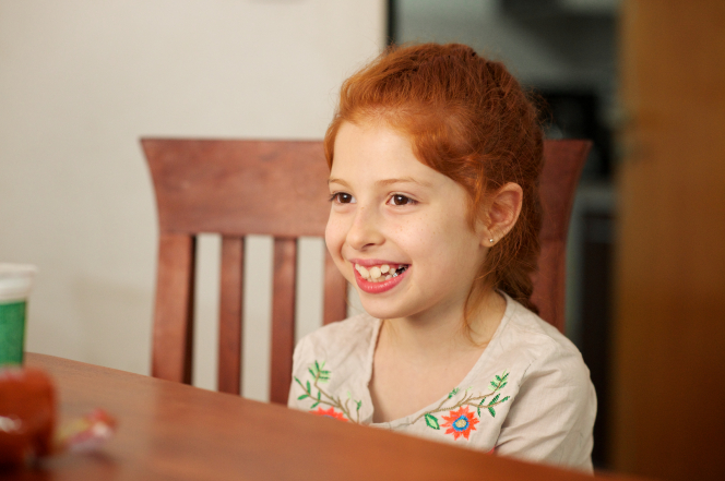 A young girl with red hair in a French braid, smiling and sitting at a dining-room table.