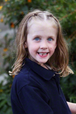 A little girl with light brown hair and blue eyes, smiling and wearing a blue polo shirt.