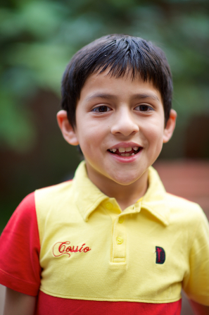 A boy from Peru with short brown hair wearing a yellow and red shirt.