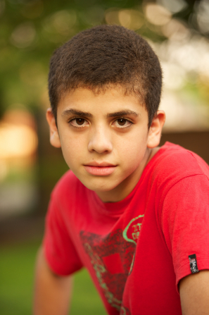 A head shot of a boy from Argentina with dark brown hair, wearing a red T-shirt.