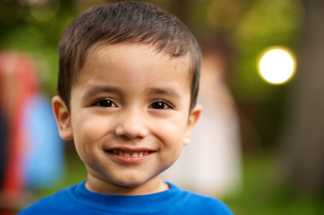 A little boy with dark brown eyes and hair, smiling and wearing a bright blue T-shirt.