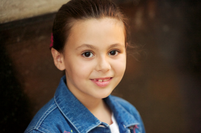 A head shot of a young girl from Argentina with brown hair and eyes, smiling and wearing a denim shirt.