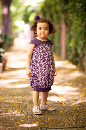 A full-body portrait of a little girl with dark curly hair standing on a sidewalk and wearing a purple cheetah-print dress.