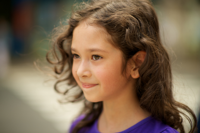 A side profile of a young girl from Argentina with wavy brown hair and brown eyes, wearing a purple T-shirt.