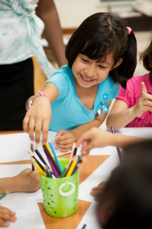 A young girl with dark brown hair and a blue shirt reaches over the table to pick out a colored pencil while drawing.