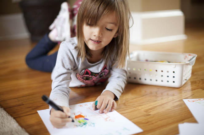 A young girl with straight brown hair lies on the floor and colors with markers on a piece of paper.