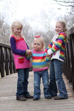 Three young sisters holding hands and standing together on a bridge, wearing jeans and rainbow sweaters.