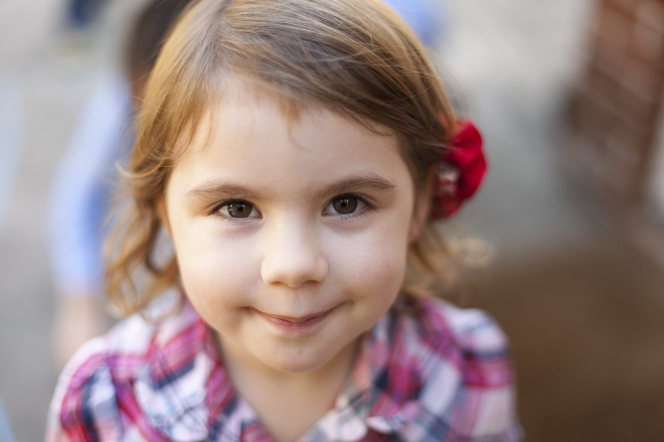 A portrait of a little girl smiling with a red flower in her hair.