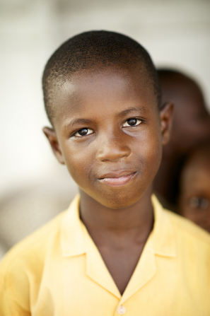 A portrait of a young boy in Ghana wearing a yellow button-up shirt.