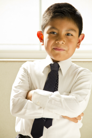 A boy in a white shirt and tie folding his arms at church.