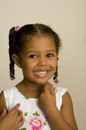 A little girl with curly hair and ponytails, smiling and wearing a white shirt with a print of a flower on it.