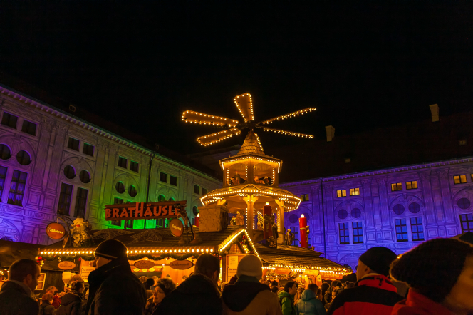 A large, illuminated Christmas pyramid overlooks a bustling Christmas market at night.