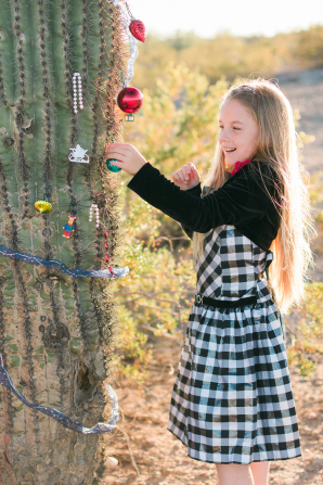 A young girl decorates a large cactus with Christmas ornaments.