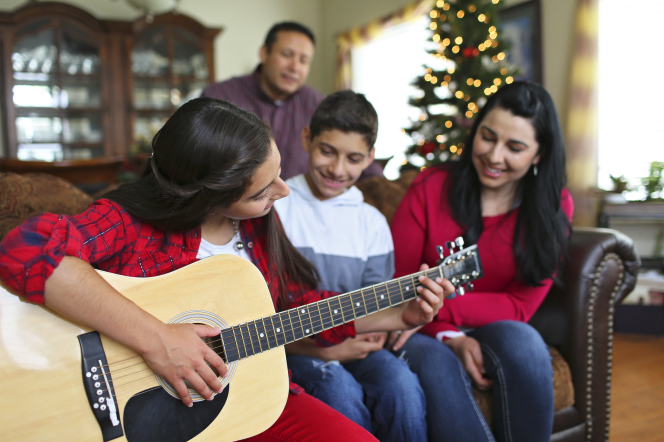 A young woman plays the guitar for her brother and parents at Christmastime.