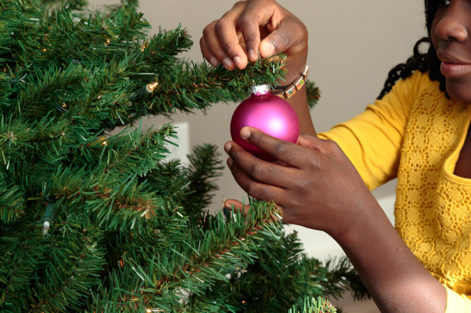 A Ghanaian girl decorates a Christmas tree with a glossy pink ornament.