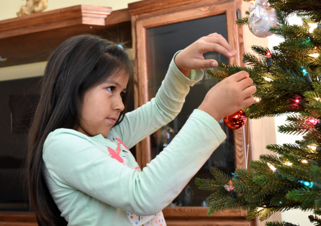 A Navajo girl decorates a Christmas tree with a shiny red ornament.