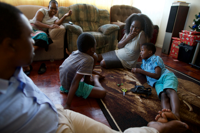 A South African family spends time together in their sitting room at Christmastime.