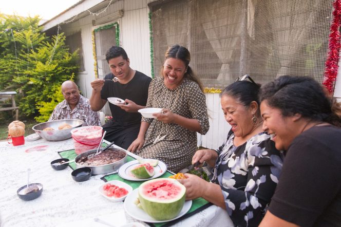 A Tongan family enjoys dessert outside.